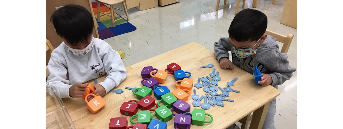 students playing with letter toys